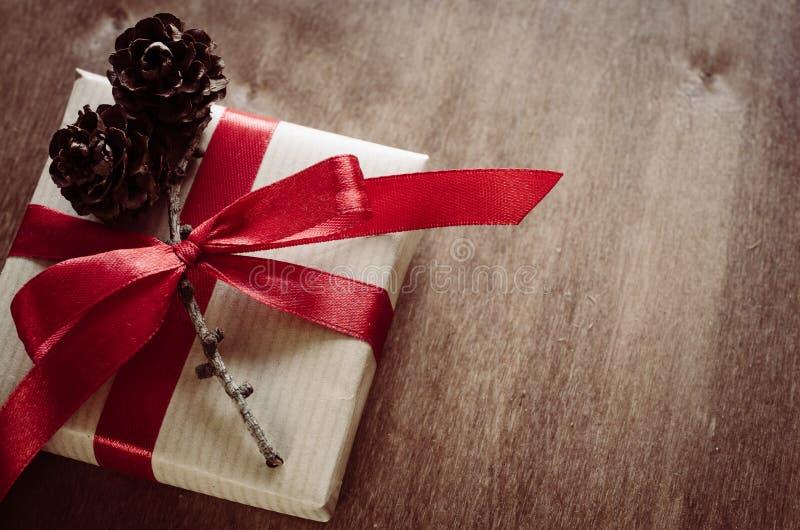 圣诞节有礼物的卡拉服特箱子,栓与红色丝带和杉木锥体在土气样式 免版税图库摄影