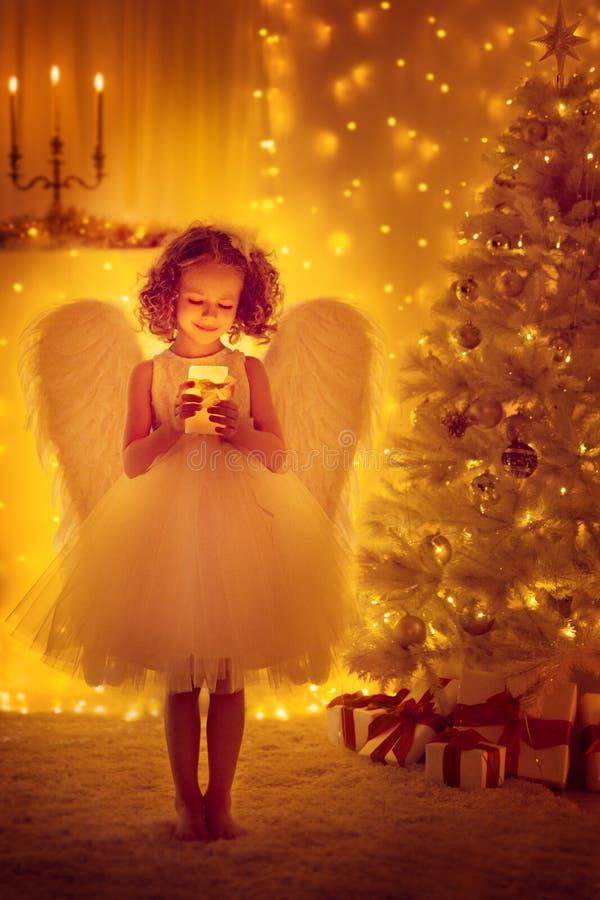 圣诞节有翼的天使孩子举行点燃蜡烛,Xmas树 免版税库存照片
