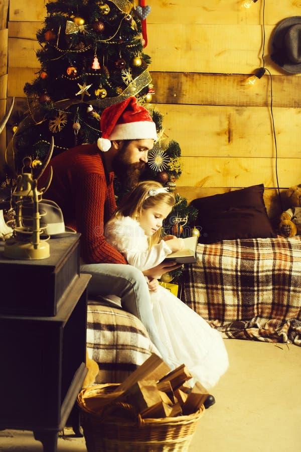 圣诞节有胡子的父亲和女孩读书 免版税库存图片