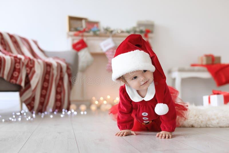 圣诞节服装的逗人喜爱的婴孩在地板上 免版税库存图片