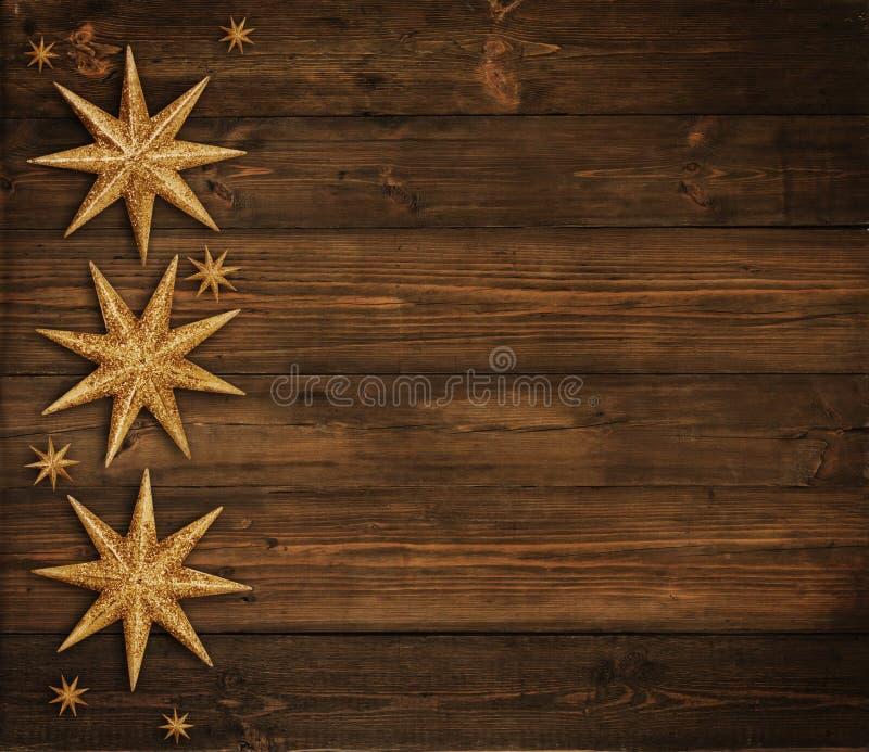 圣诞节木背景,金黄星装饰,布朗木头 免版税图库摄影