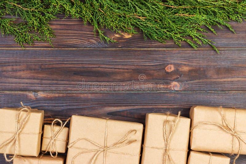 圣诞节杉树分支与在黑暗的土气木背景的礼物盒与文本的拷贝空间 库存照片