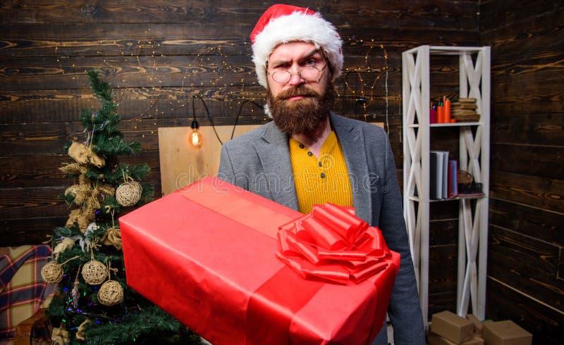 圣诞节来 圣诞老人传讯者 礼物交付 人圣诞老人帽子交付礼物 被传播的幸福和喜悦 有胡子的人 免版税库存照片