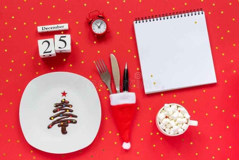 圣诞节构成日历12月25日甜巧克力在板材,在圣诞老人帽子杯的利器的圣诞树可可粉 免版税库存照片