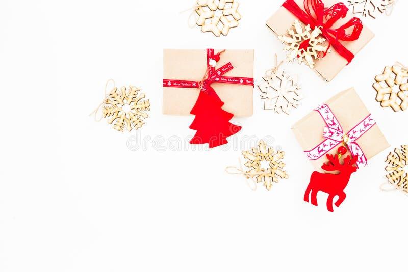 圣诞节构成由纸礼物盒和装饰制成在白色背景 平的位置,顶视图 新年框架概念 免版税库存照片