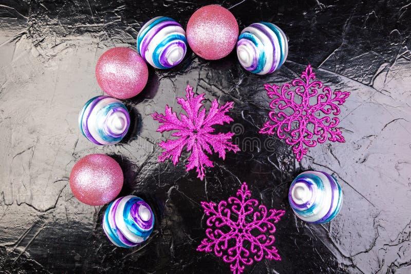 圣诞节桃红色和紫色球和装饰雪花在黑背景 平的位置 库存照片