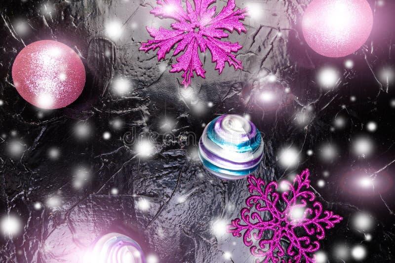 圣诞节桃红色和紫色球和装饰雪花在黑背景 平的位置 免版税库存照片