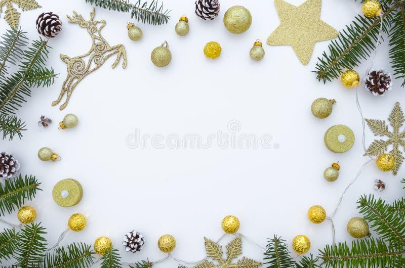 圣诞节框架由冷杉分支、欢乐装饰、礼物盒和杉木锥体,在白色桌上的金黄诗歌选做成 库存照片