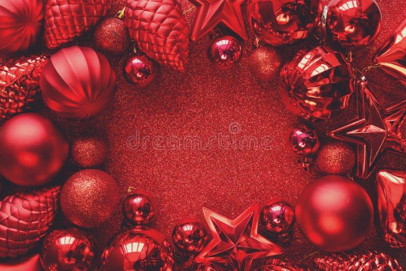 圣诞节框架红色 圣诞节球、星、锥体和心脏在红色闪闪发光背景 平的位置 顶视图 免版税库存图片