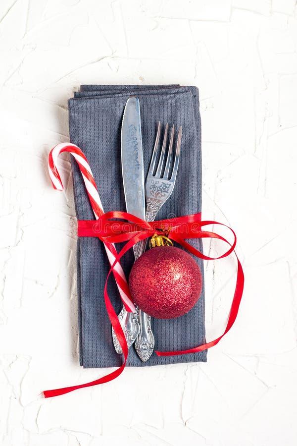圣诞节桌与刀子、叉子、红色球、棒棒糖和丝带的餐位餐具在与copyspace的白色桌 免版税图库摄影