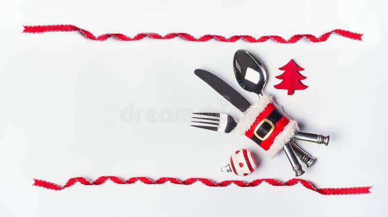 圣诞节桌与利器的餐位餐具,红色丝带框架和装饰,在白色桌面背景,顶视图的拷贝空间 库存照片