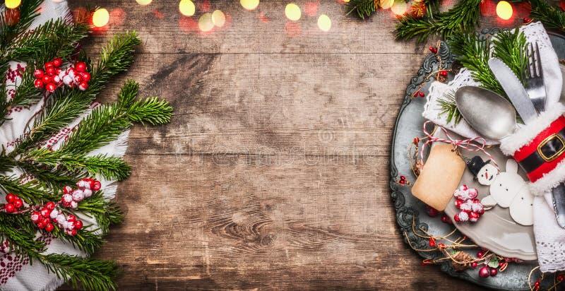 圣诞节桌与欢乐装饰、板材、利器、手工制造雪人和空白的标记的餐位餐具在土气木背景,上面 免版税库存照片