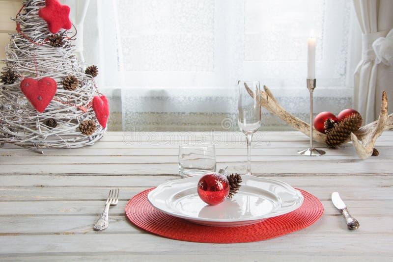 圣诞节桌与白色餐具、利器、银器和红色装饰的餐位餐具在ligth内部的白色木板 库存图片