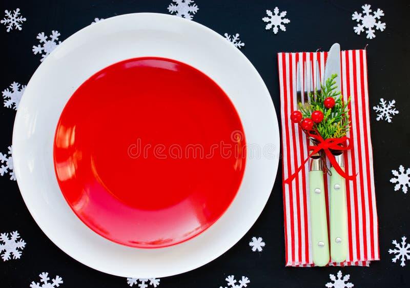 圣诞节桌与空的红色板材的餐位餐具,圣诞节de 库存图片