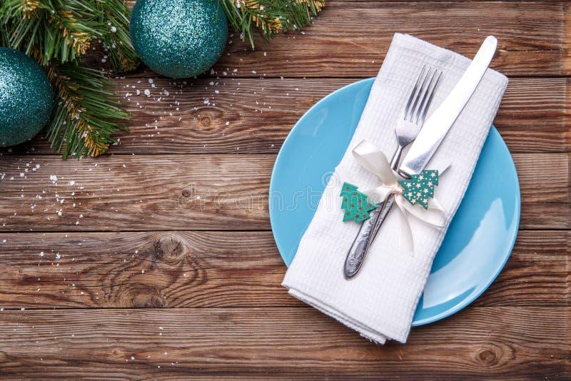 圣诞节桌与蓝色板材的餐位餐具、叉子和刀子、装饰的丝带和弓与冷杉木玩具,白色餐巾 免版税库存图片