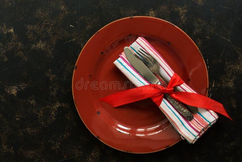 圣诞节桌设置、红色板材、葡萄酒利器和餐巾栓了与在黑暗的土气背景的一条丝带 顶视图,平的位置 免版税库存照片