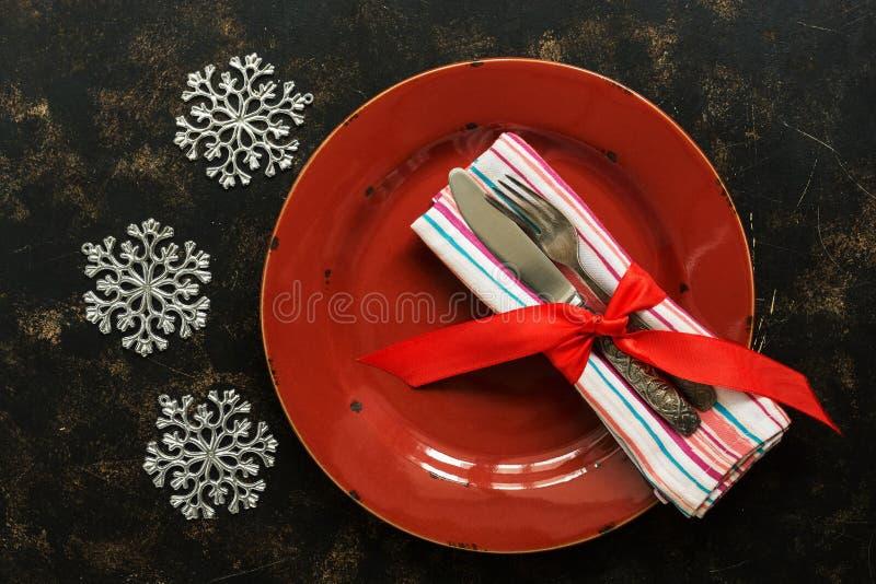 圣诞节桌设置,空的红色板材,在用雪花装饰的黑暗的土气背景的葡萄酒利器 顶视图,平的位置 免版税库存照片