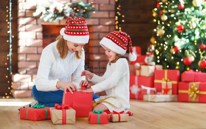 圣诞节森林上了凸边早晨多雪的线索宽冬天 家庭母亲和女儿打开,开放礼物 库存照片