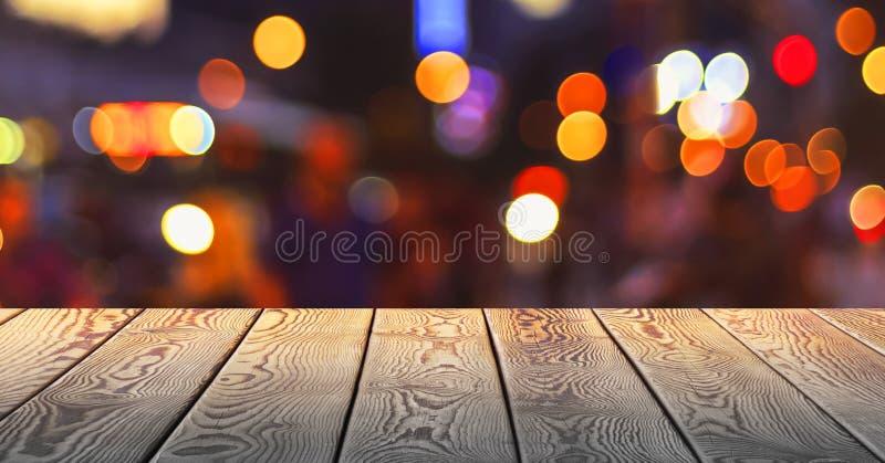 圣诞节概念:与亮点的欢乐在一张空的木桌前面的背景和bokeh 免版税库存图片
