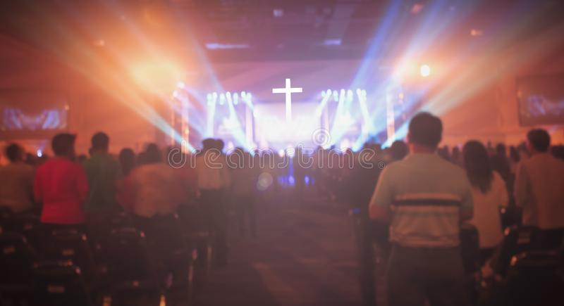 圣诞节概念:被弄脏的基督徒会众崇拜上帝一起在音乐阶段前面的教会光线影响的大厅和里 免版税图库摄影