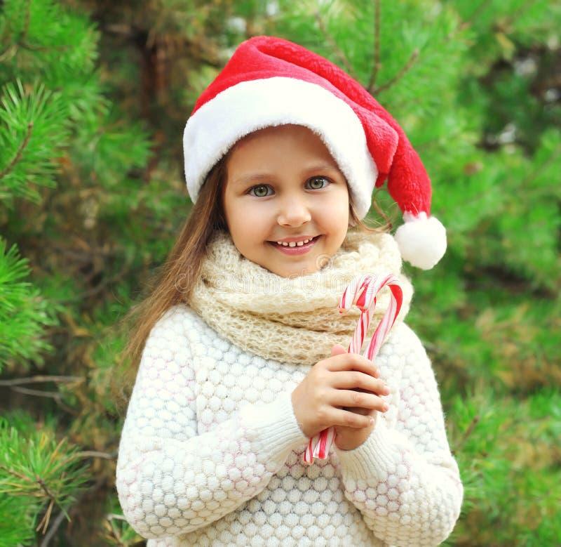 圣诞节概念-圣诞老人红色帽子的画象小微笑的女孩孩子有甜棒棒糖藤茎的 免版税库存照片