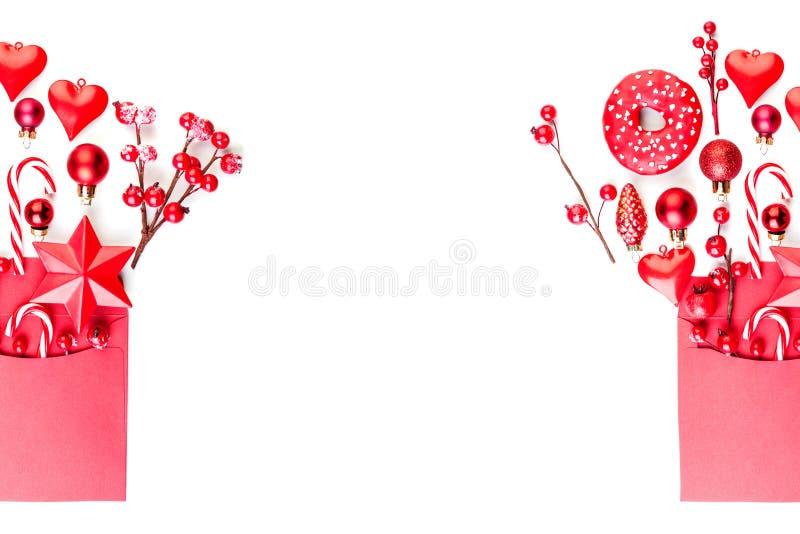 圣诞节横幅背景霍莉莓果、星和装饰在白色隔绝的红色信封 Xmas舱内甲板被放置的顶视图 免版税库存图片