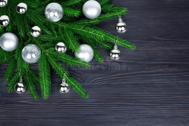 圣诞节欢乐壁角边界,新年装饰框架,在绿色冷杉分支的发光的银色玻璃球装饰在黑色 库存图片