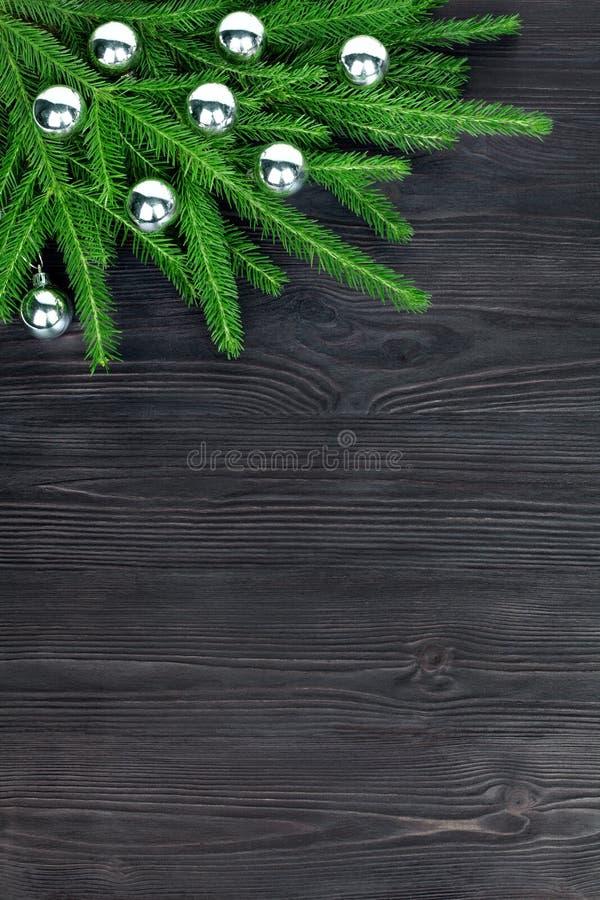 圣诞节欢乐壁角边界,新年装饰框架,在绿色冷杉分支的银色玻璃球装饰在黑木头 免版税库存照片
