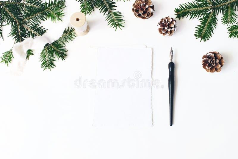 圣诞节欢乐构成 信封和白纸贺卡大模型场面 杉树分支边界 背景锥体查出的对象杉木白色 免版税库存照片