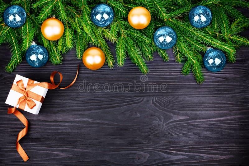 圣诞节欢乐边界,在绿色冷杉分支,在黑色的礼物盒的新年装饰框架,金黄和蓝色球装饰 免版税库存图片