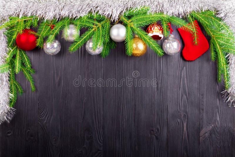 圣诞节欢乐边界,新年装饰框架,银色球装饰,在绿色杉木分支的红色礼物袜子在黑木头 免版税库存图片