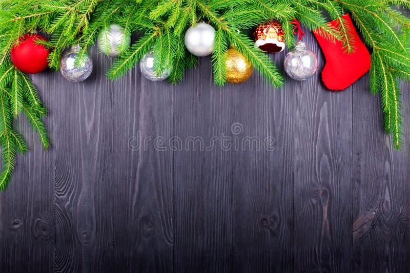 圣诞节欢乐边界,新年装饰框架,银色球装饰,在绿色杉木分支的红色礼物袜子在黑木头 图库摄影