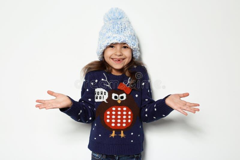 圣诞节毛线衣和被编织的帽子的逗人喜爱的女孩 库存图片