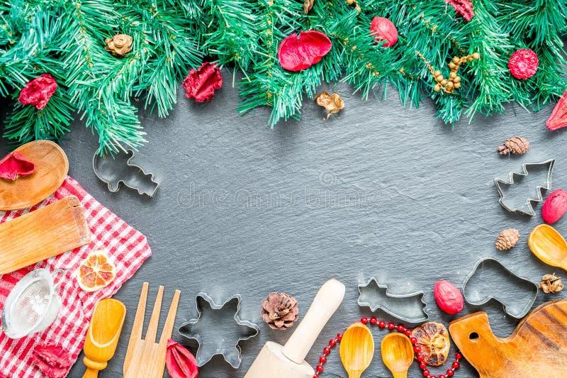 圣诞节炊事用具和圣诞树在黑暗的石背景,顶视图 免版税库存照片