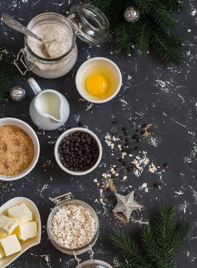 圣诞节烘烤背景 面粉,糖,黄油,燕麦片,鸡蛋,在黑暗的背景的巧克力片 图库摄影