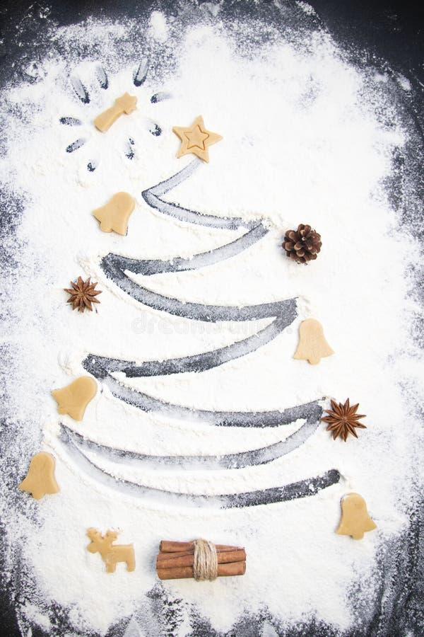 圣诞节烹调:由面粉做的杉树在一张黑暗的桌、成份烘烤的和干果子在黑暗的背景 免版税图库摄影