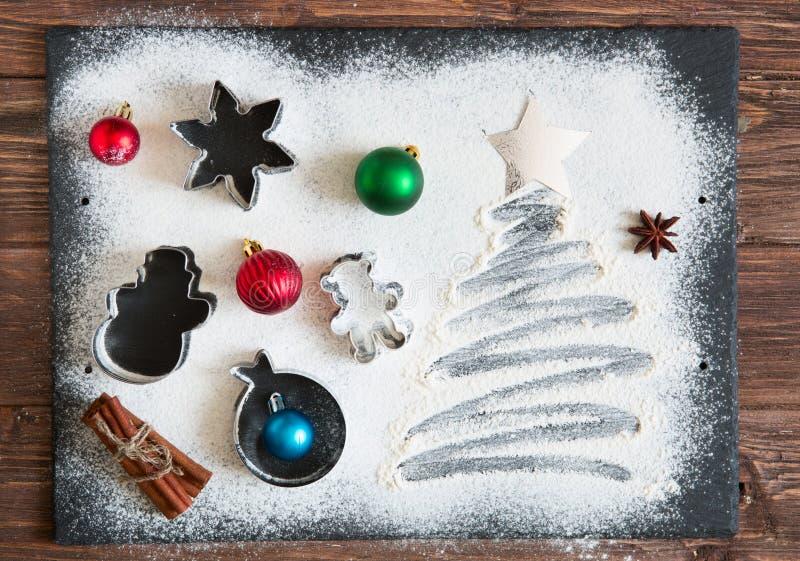 圣诞节烹调 由面粉做的Xmas树在一张黑暗的桌,烘烤的成份在黑暗的背景,顶视图 免版税库存图片