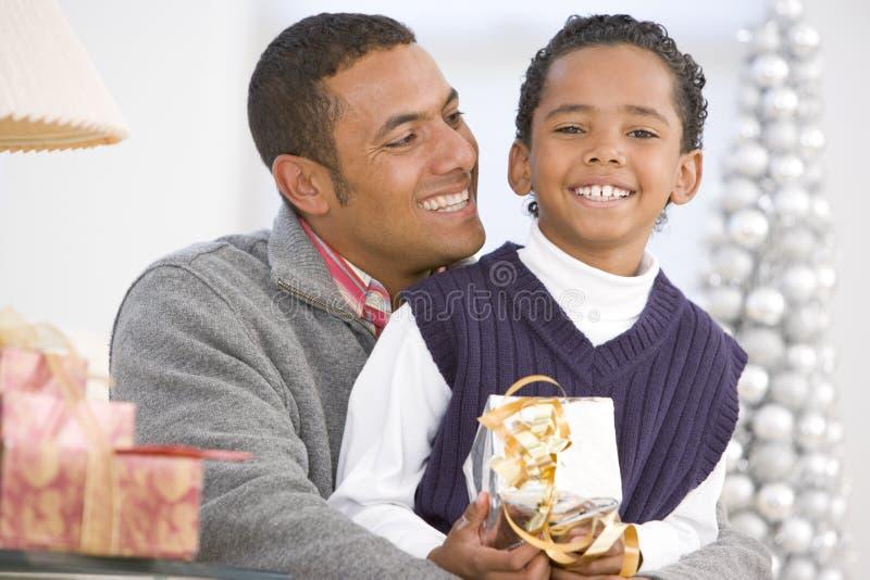圣诞节父亲拥抱儿子的礼品藏品 免版税库存图片