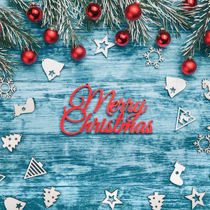 圣诞节玩具、冷杉分支和红色中看不中用的物品品种在蓝色木背景 平的位置,顶视图 库存图片