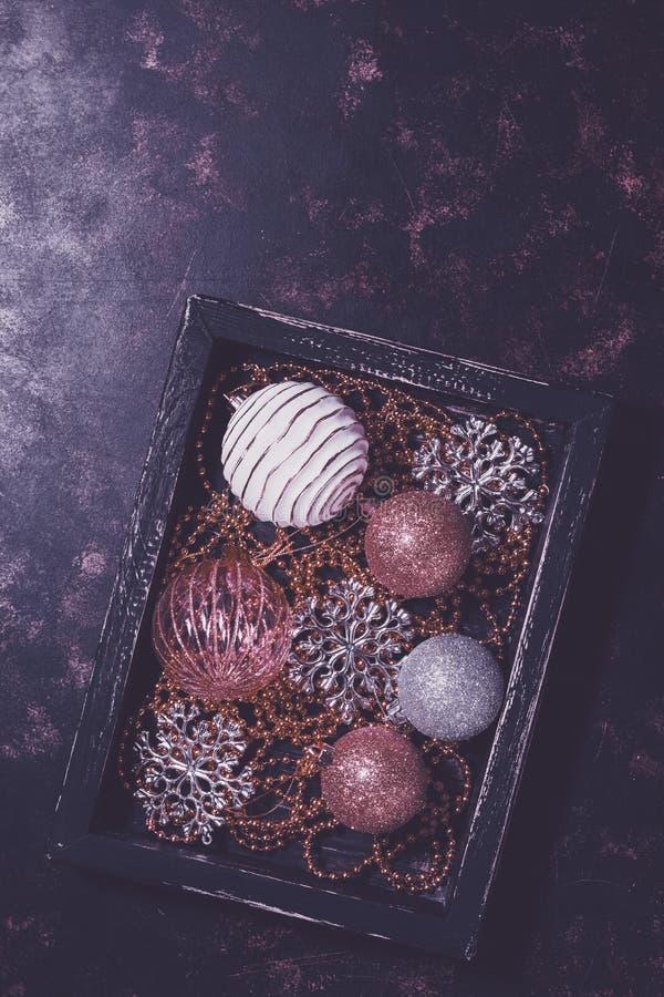 圣诞节玩具球和雪花在一个木箱在土气背景 顶视图,拷贝空间,purupr定了调子 库存照片