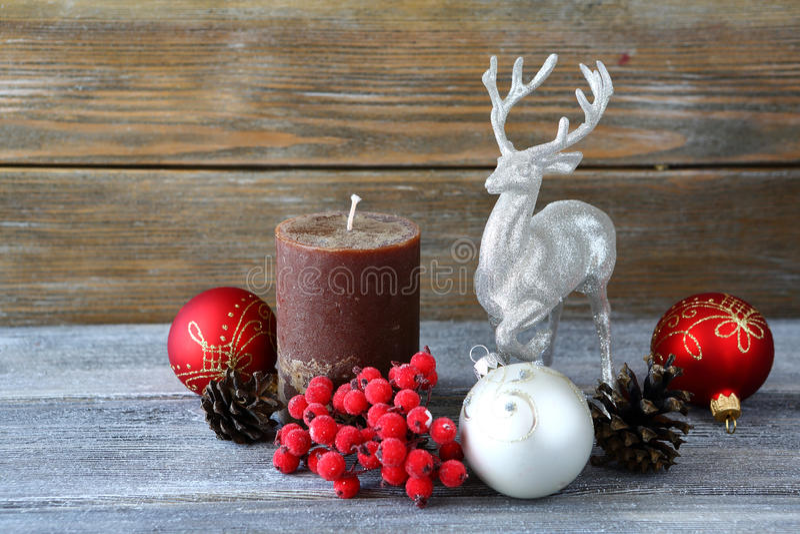 圣诞节球、蜡烛与杉木锥体和一头鹿在委员会 库存图片