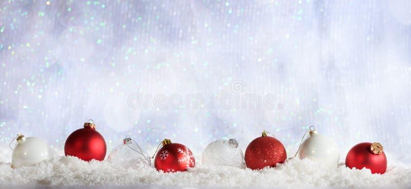 圣诞节球在圣诞节多雪的bokeh背景荡桨 库存照片