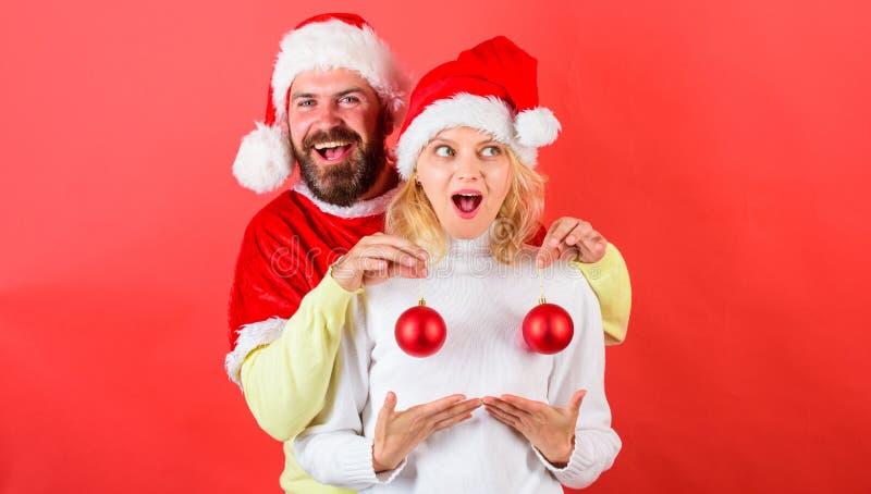 圣诞节球标志植入管女性乳房 夫妇激动的举行圣诞节球 圣诞节奇迹概念 塑料 免版税图库摄影