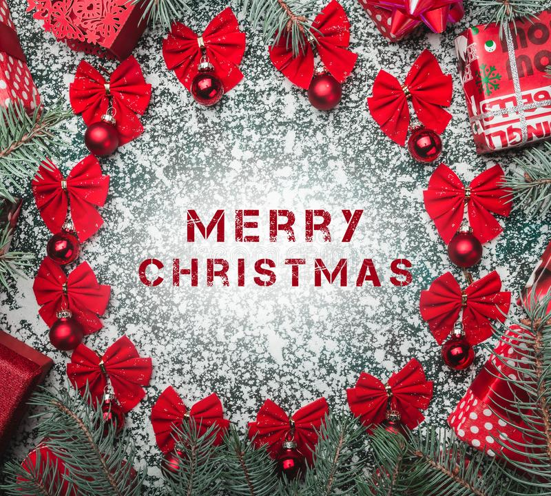 圣诞节球特写镜头视图装饰了红色弓、冷杉分支和新年礼物在背景与雪花 库存图片