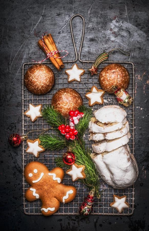 圣诞节甜烘烤食物:自创姜饼,曲奇饼, stollen用香料、冷杉分支和红色假日装饰在黑暗 免版税库存图片