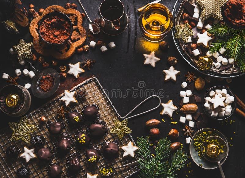 圣诞节甜背景用巧克力、蛋白软糖、曲奇饼、自创果仁糖、恶、坚果和精神在黑暗的土气桌上 库存照片