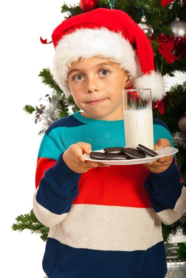 圣诞节男孩hoilding的牛奶和饼干 免版税库存图片