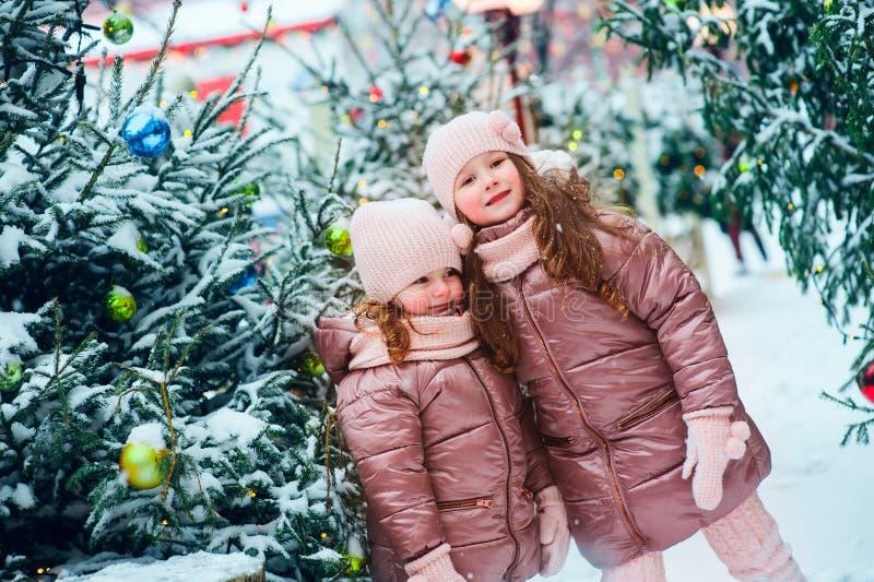 圣诞节画象两个愉快姐妹使用室外在新年假日装饰的冬天多雪的城市 库存图片