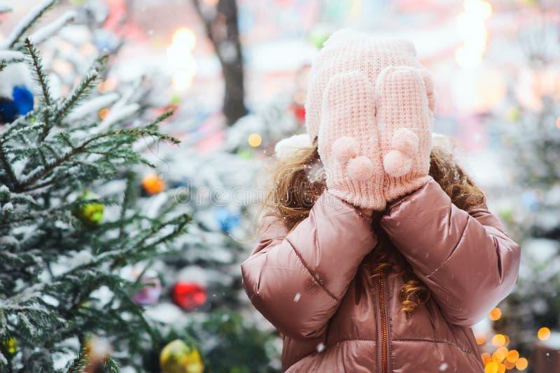 圣诞节画象愉快孩子女孩使用室外在多雪的冬日,在新年假日装饰的冷杉木 免版税库存照片