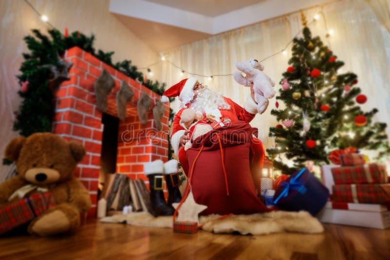 圣诞节的圣诞老人与礼物袋子在Th旁边打开箱子 免版税库存照片